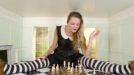 Young woman playing chess in small room, zoom in