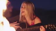 MS Young woman playing guitar and singing at campfire at dusk / Lake Powell, Utah, USA