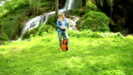 Young woman playing guitar by waterfall in summer