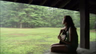 Young woman playing guitar under shelter in park on rainy day / Connecticut