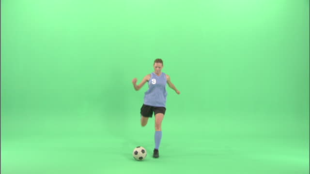 WS, Young woman playing soccer in studio
