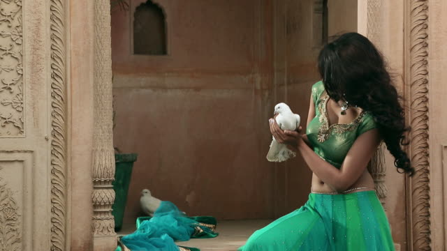 Young woman playing with a pigeon, Nahar Singh Palace, Haryana