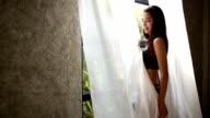 Junge Frau spielt mit Vorhang