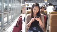 Young woman playing with Smart hone while waiting for her flight, Slow motion