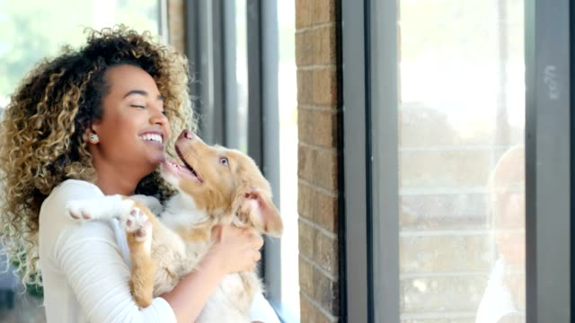 Young woman plays with adorable puppy