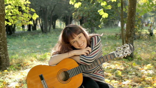 Young woman posing, flirting, holding guitar in park, summer.