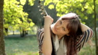 Young woman posing in park, flirting, holding guitar, smiling outdoors.