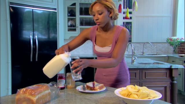 A young woman pours a glass of milk to go with her sandwich and walks out of the shot.