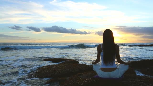 Giovane donna praticare yoga vicino al mare al tramonto