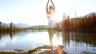 Young woman practicing yoga moves at sunset