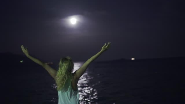 Ung kvinna be på stranden. Full moon.