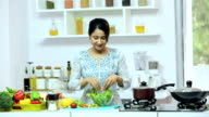 MS Young woman preparing food in kitchen