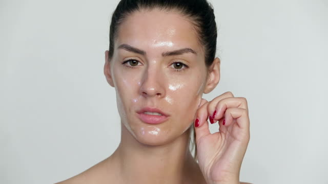 Young woman pulling peel off facial mask