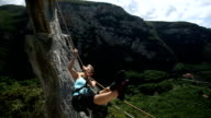 Young woman pulls herself across Tyrolean traverse