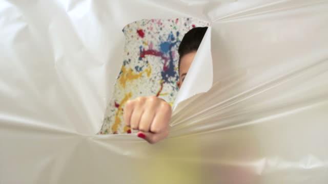 Young woman punching through plastic sheet, slow motion