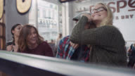 WS. Young woman puts her arm around man and gives him a noogie as friends laugh in local coffee shop window.