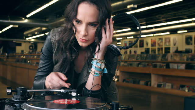 A young woman puts on a reocrd and listens to a song in a record store.