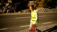Young woman putting emergency sign on the road