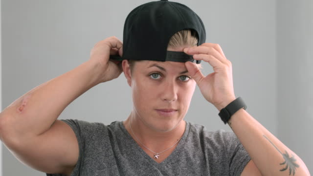 Young woman putting on baseball cap
