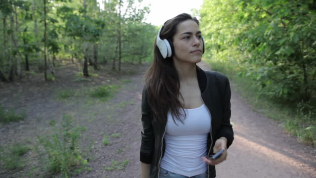 Young woman putting on headphones, walking, smiling in park in Berlin