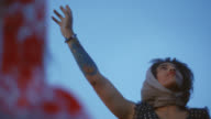 Young woman raises hand to the blue sky and looks off as the wind blows on desert road trip.