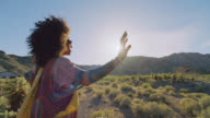 SLO MO. Young woman raises hands in the air under desert sun.