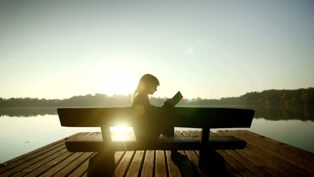 Young woman reading a book by the lake