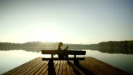 Young woman reading a book on a bench by lake