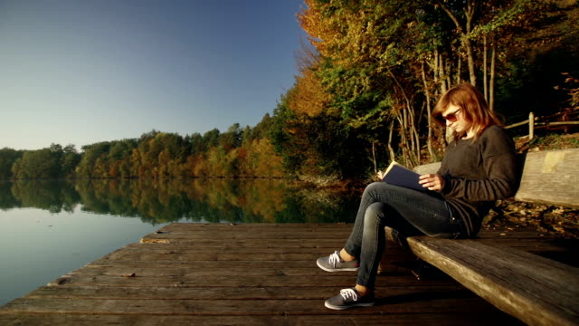 Young woman reading a book on bench by the lake
