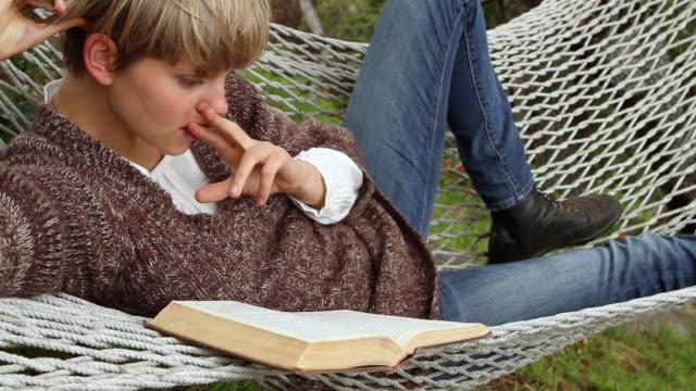 MS Young woman reading book in hammock / Big Sur, California, USA
