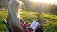 Giovane donna lettura libro nella natura