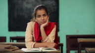 Young woman reading book in the classroom, Haryana, India