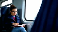 Young woman reading on a train