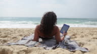 Young woman reading on tablet laying at the beach in the South of France.