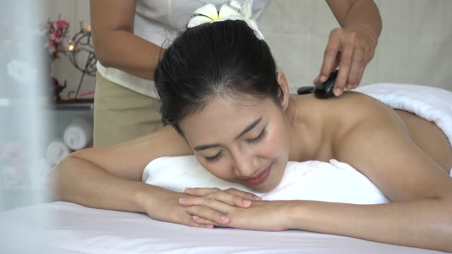 Young woman receiving back massage and hot stone spa