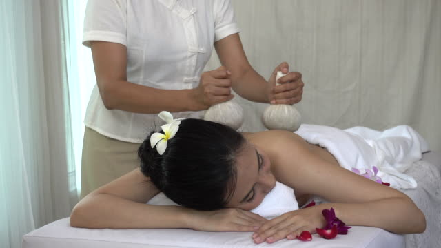 Young woman receiving back massage with Thai Herbal Compress Ball