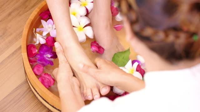 Young woman receiving foot spa massage
