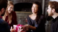 Young woman receiving gift from friends during Christmas
