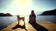 Young woman relax sitting on pier at the lake with dog