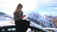 Young woman relaxes on roof of car, sending text