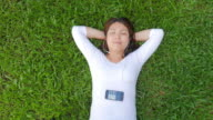 Young woman Relaxing and listening to music on green grass