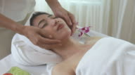 Young woman relaxing and receiving face massage