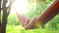 Young woman relaxing in a hammock under the trees