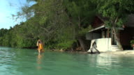 Young woman relaxing in wild ocean by her bungalow