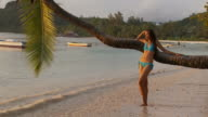 WS Young woman relaxing on beach / Seychelles