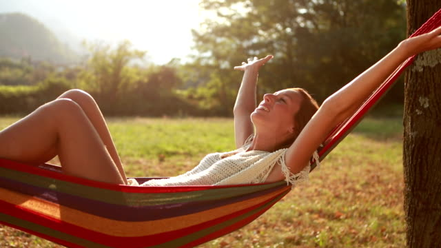 Young woman relaxing on hammock, arms outstretched