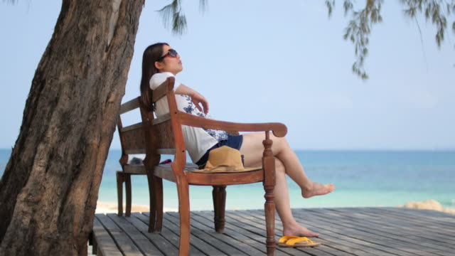 Jonge vrouw ontspannen op het strand in de buurt van de zee in de zomertijd, ontspanning concept, 4k(UHD)