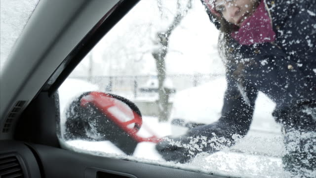 Young woman removing snow off the car window and mirror.
