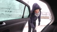 Young woman removing the snow from a car.