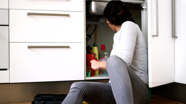 Young woman repairing sink with work tool